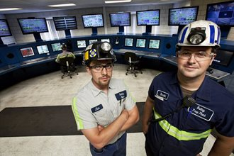 Two men in hard hats standing in a control room